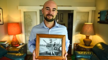 Duncan Williams holds a photo of his WWII RAAF pilot grandfather sitting on the wing of a Spitfire plane.