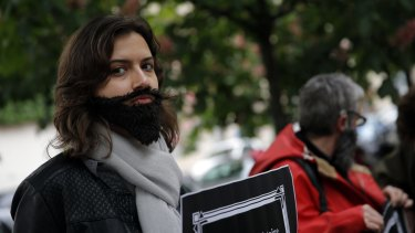 A woman with a fake beard attends a Paris protest on Wednesday to demand an end to widespread sexism in French politics.