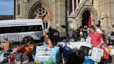 People leave donations outside the Notting Hill Methodist Church near the burning 24-storey residential Grenfell Tower block.