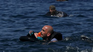 A Syrian father holding a baby in a lifetube swims towards the shore after their dinghy deflated some 100m away before reaching the Greek island of Lesbos.