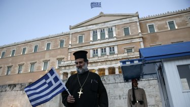A priest walks past the presidential guard during an anti-austerity rally at Greece's parliament on Wednesday.