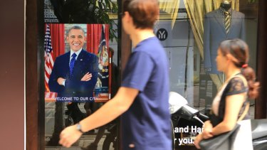 A Vietnamese couple pass a poster of US President Barack Obama hanging in a door in Hanoi.