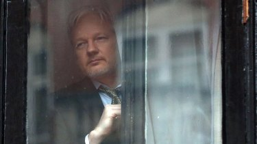 Julian Assange looks out from the Ecuadorian embassy in London,  where he took refuge in June 2012 to avoid extradition to Sweden.