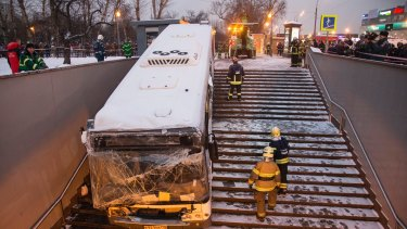 Emergency personnel work to pull a bus that crashed down subway stairs in Moscow on Monday.