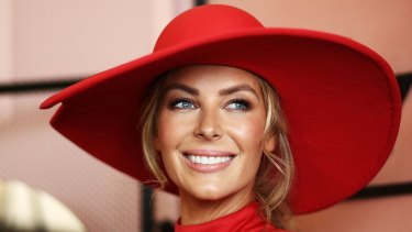 Jennifer Hawkins in a red jumpsuit by Misha Collection. And hat.