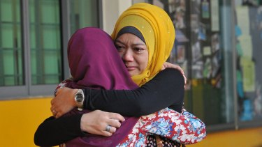Family members of students from Tanjong Katong Primary School embrace.