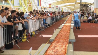 The world's longest pizza shortly before it was devoured in Milan on Saturday.