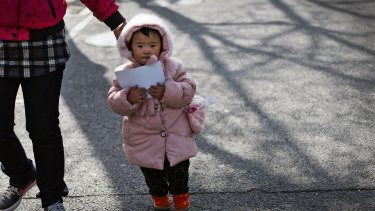A woman leads a child in Beijing. China's ruling Communist Party announced that it will abolish the country's decades-old one-child policy.