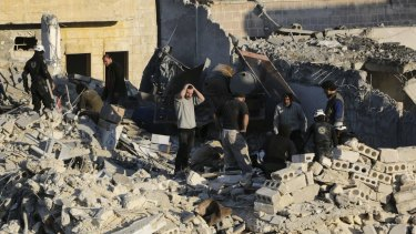 Civilians caught in the war: People look for survivors amid debris after barrel bombs were reportedly dropped by forces loyal to Bashar al-Assad in Aleppo.