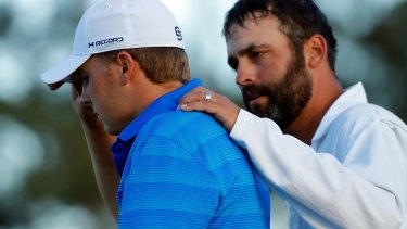 Jordan Spieth is comforted by caddie Michael Greller after imploding on the last nine holes of the Masters on Sunday.