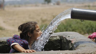 A girl drinks water from an irrigation tube in northern India's Jammu region during a May heatwave.