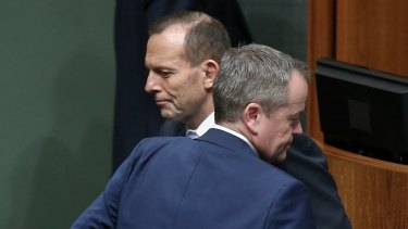 Prime Minister Tony Abbott and Opposition Leader Bill Shorten cross paths during a division in the House of Representatives.