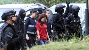 Indonesian suspect Siti Aisyah, center, is escorted by police officers as she arrives in court on Wednesday.