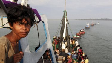 A fishing boat carrying Rohingya and Bangladeshi migrants is pulled to shore by Achenese fisherman in May.