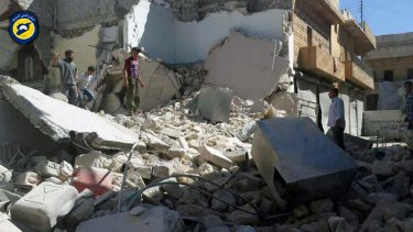 In a picture provided by the Syrian Civil Defence/White Helmets group, Syrians inspect damaged buildings after air strikes hit the Bustan al-Qasr neighbourhood of Aleppo.