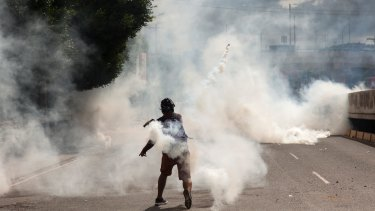 A supporter of Libre Alliance presidential candidate Salvador Nasralla returns a canister of tear gas launched by riot police in Tegucigalpa, Honduras.