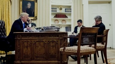 Donald Trump, left, on the phone with Australian PM Malcolm Turnbull, as Michael Flynn, US national security advisor, centre, and Steve Bannon, wait.