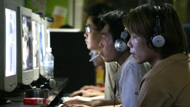 Chinese hackers can be both from the government and freelance. Pictured: Chinese youths surf the net at a cyber cafe in Shanghai, China.