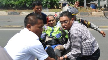 People carry an injured police officer near the site where an explosion went off at a police post in Jakarta last week.