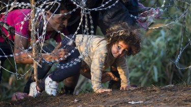 A child is helped to cross from Serbia to Hungary through the barbed wire fence near Roszke.