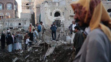 People stand on the rubble of houses at the site of a Saudi-led airstrike near Yemen's Defense Ministry complex in Sanaa, in November.