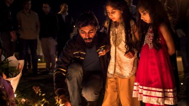 Adnan Amjid, a friend and housemate of Zeeshan Akbar, helps girls light candles at a vigil outside a Caltex service station in Queanbeyan where the 29-year-old Caltex attendant was fatally stabbed.