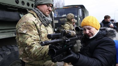 A member of the US Army's 2nd Cavalry Regiment shows a gun to a woman during the ''Dragoon Ride'' military exercise in Salociai, northern Lithuania. US troops will travel through Lithuania, the Czech Republic and on to Germany by April 1 to reinforce US allies in Eastern Europe.