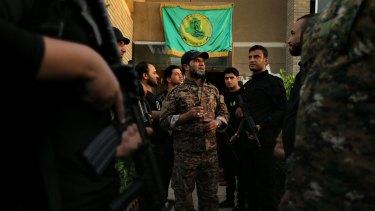 Haji Jaffer al-Bindawi, a leader of the Imam Ali Brigades, an Iraqi Shiite militia fighting Islamic State, with  his men  in Baghdad  in October 2014.