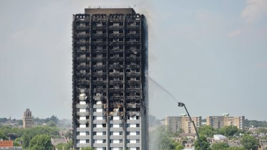 Firefighters spray water onto the 24-storey apartment block in west London on Wednesday.