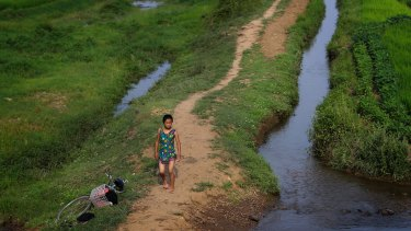 A young girl dressed in her swimming suit walks by a stream between fields in North Korea's Hamju district this week.