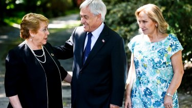 Chilean President Michelle Bachelet, left, talks with president-elect Sebastian Pinera, a former president, as Pinera's wife Cecilia Morel looks on.