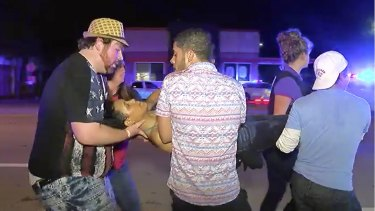 An injured person is escorted out of the Pulse nightclub in Orlando after being shot.