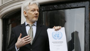 Julian Assange, pictured on the balcony of Ecuador's London embassy, holds the UN report that says he is being 'arbitrarily detained' by Britain and Sweden.