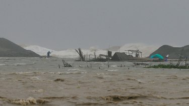 A Philippine fisherman works on his destroyed fish cages amidst huge waves brought about by Haima.