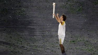 Gustavo Kuerten carries the Olympic torch.