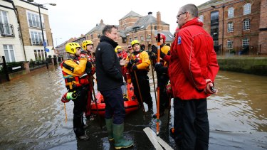 British Prime Minister David Cameron meets rescue teams working on flood relief in York city centre.