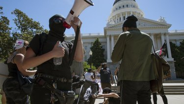 Members of the group called ANTIFA Sacramento (Anti-Fascism Action) try to light a flag on fire as they stage a counter-protest against skinheads at the California state Capitol in Sacramento, California.