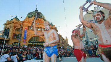 Aboriginal dancers perform  at the intersection of Flinders Street and Swanston Streets.