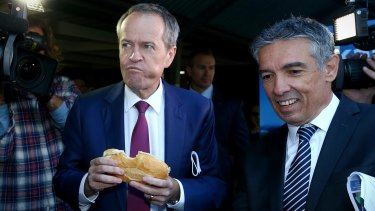 Opposition Leader Bill Shorten eats a sausage together with the ALP candidate for Reid, Angelo Tsirekas, during a visit to a polling booth on Saturday.