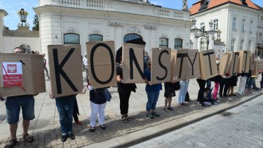 """People hold boards with the word """"Constitution"""" in front of the presidential palace Warsaw, Poland on July 24."""