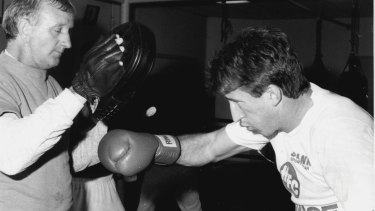 League of his own: Lewis trains with Canterbury Bulldogs captain Steve Mortimer during a ring session at Newtown.