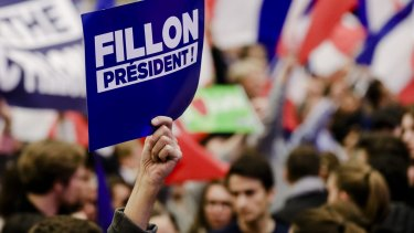 A supporter holds up a sign during an election campaign meeting for France's presidential candidate Francois Fillon.