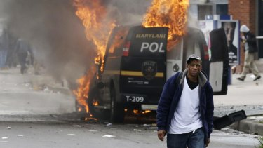 A man walks past a burning police vehicle, during unrest following the funeral of Freddie Gray in Baltimore.