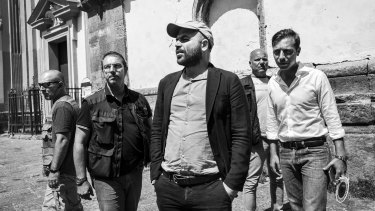 Roberto Saviano, centre, an Italian journalist, writer and essayist, with his police escort in Naples, Italy.