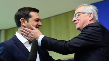 Greece's Prime Minister Alexis Tsipras (left) is welcomed by European Commission President Jean-Claude Juncker ahead of an emergency leader's summit in Brussels.
