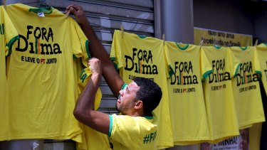 A vendor hangs shirts reading 'Out, Dilma' during a protest against Brazil's President Dilma Rousseff in Sao Paulo on Sunday.