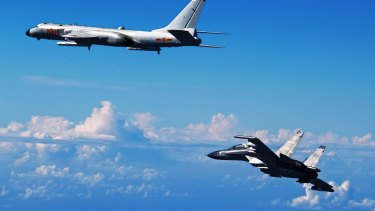 A Chinese People's Liberation Army Air Force Su-30 fighter, right, flies along with a H-6K bomber as they take part in a drill near the East China Sea in September.