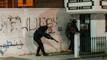 Riot policemen hide behind a wall during anti-government protests in Tunis.