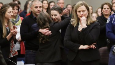 Former gymnast Rachael Denhollander, centre, is hugged after giving her victim impact statement.