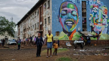 Women walk past their apartment block in the low-income neighbourhood of Mbare in Harare.